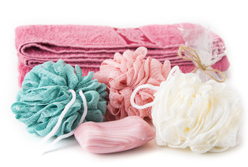 Bath sponges with soap and towel on the white background