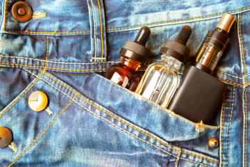 Electronic cigarettes in the pocket of jeans. VAPE