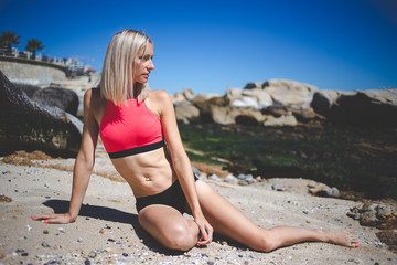 Sexy blond female fitness model posing on the beach with a sexy bikini