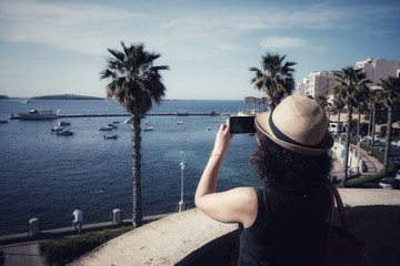 girl takes pictures of the panorama of Bugibba in Malta