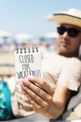 man with a note with the text closed for vacation.