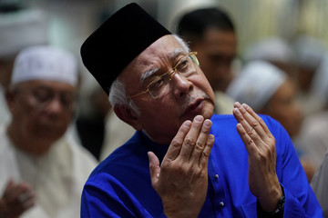 Malaysia's Prime Minister Najib Razak offers special prayers a day before the 14th general election at a mosque in Pekan, Pahang