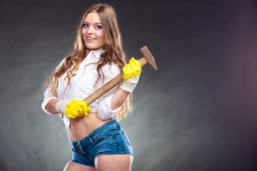 Sexy alluring woman holding hammer. Feminism.