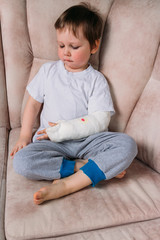 a small boy is sitting on a chair with a broken arm, in a cast. hospital. medicine. danger. pain. to break limbs. violence.