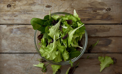 Fresh salad leaves in bowl on wooden table. Natural organic nutrition concept.