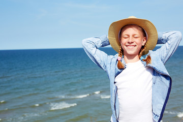 Happy child on a turquoise sea background. Recreation concept - positive emotions. Horizontal photo