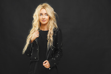 portrait of stylish girl with blond hair in the style of swags in black clothes against a dark background.