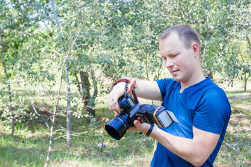 Portrait of attractive male photographer at work looks to camera. Summer day. Young man with a DSLR camera in hands. One person portrait with copy space.
