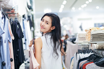 Young woman chooses clothes in a clothing store