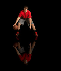 Young athlete in red tee shirt playing basketball on reflective, black surface