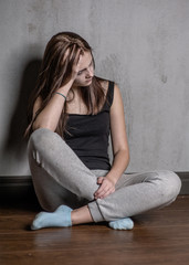 Sad teen girl sit on the floor