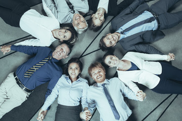 Eight smiling at camera business people lying on floor in circle and holding hands. Top view.
