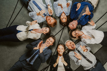 Eight smiling at camera business people lying on floor in circle and clapping. Top view.