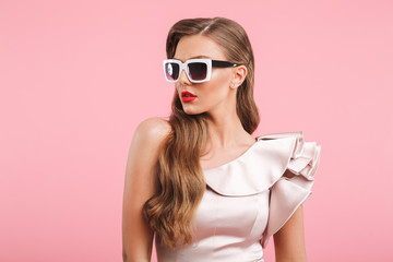 Portrait closeup of fashionable woman 20s in dress looking aside in stylish square sunglasses, isolated over pink background