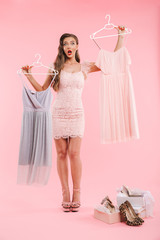 Full length photo of doubting young woman 20s choosing dresses on hangers while shopping, isolated over pink background