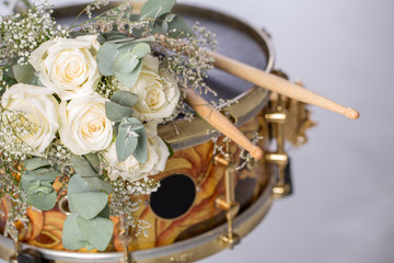 The white rose drumsticks is placed on a snare drum. There are nobody. Black space circle for your text.
