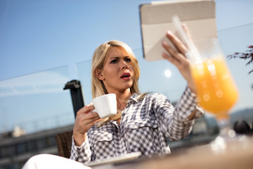 young woman in cafe with cup of coffee and touchscreen tablet while siting in cafe