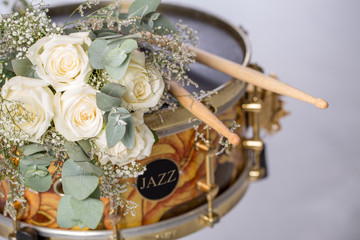 """The white rose drumsticks is placed on a snare drum. There are nobody. There is text """"JAZZ"""" on black circle space beside the drum."""