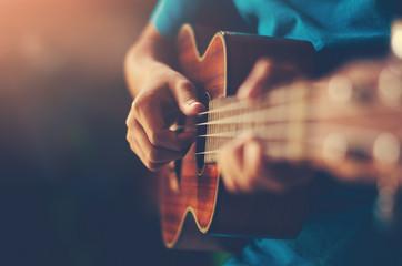 Hands playing acoustic guitar ukulele