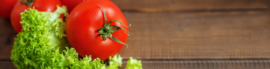 Tasty tomato and lettuce on a wooden background. Banner for website.  The concept of healthy eating and vegetarianism.