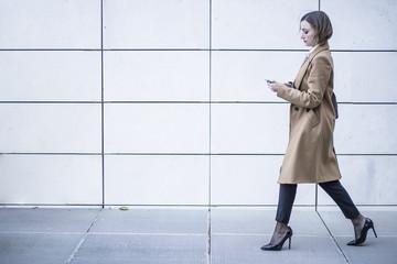 Manager con con cappotto beige e tacchi cammina velocemente con in  mano il suo cellulare - sfondo parete bianca a righe nere