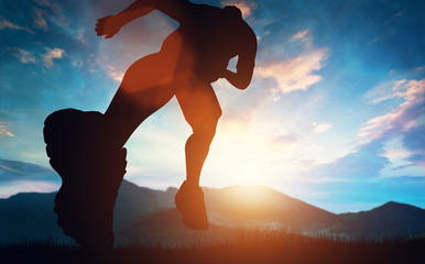 Man running towards the sunset in the mountains