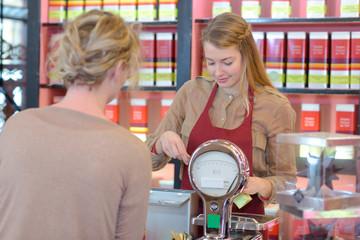 ordinary female buyers choosing tea on grocery shelves
