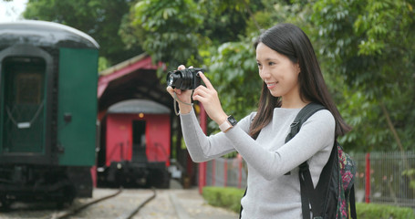 Woman travel and taking photo on digital camera at train station