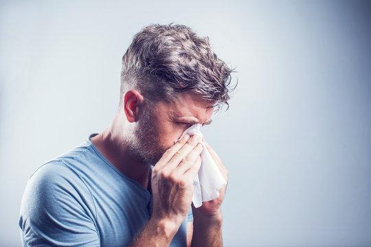 Man sneezing in a tissue outdoors. Pollen allergy, Springtime.