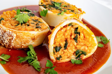 roasted breaded calamari stuffed with rice and spinach cut open in placed tomato sauce and decorated with parsley