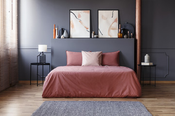 Real photo of a simple bedroom interior with dirty pink bedding on the bed standing against dark gray wall with molding, between two, metal bedside tables