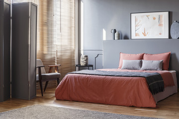 Real photo of elegant bedroom interior with black walls, brown blinds and orange sheets on gray bed