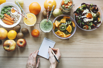Crop hands making notes near healthy food