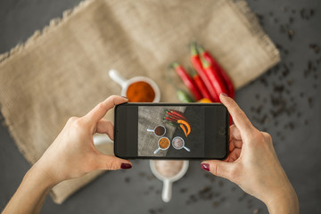 Top view of a blogger taking a photo of spices in stylish ceramic dishes for her culinary blog with a smartphone