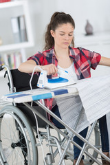 girl on the wheelchair ironing clothes