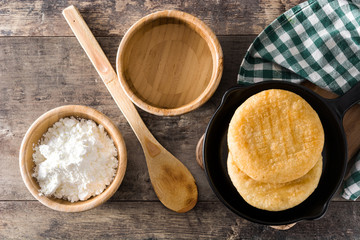 Arepas in iron pan on wooden table. Venezuelan typical food. Top view