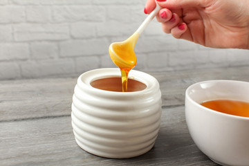 Detail on woman holding small ceramic  spoon, filled with honey, about to put it in white tea cup full of hot tea.