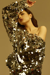 Wall Mural - Sensual beautiful brunette woman in a shiny fashion dress of sequins