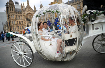 People dressed in wedding attire ride in a horse drawn carriage through Westminster in central London