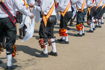 diagonal line of traditional english morris dancers wearing plus fours bells and sashes