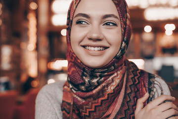 beautiful muslim girl in hijab sits in an arabian cozy cafe and smiles