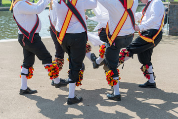 group of morris dancers wearing sashes and bells dance in a circle