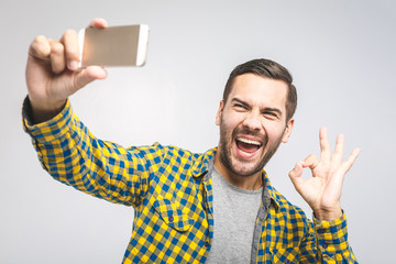 I love selfie! Handsome young man in shirt holding camera and making selfie and smiling while standing against grey background. Ok sign