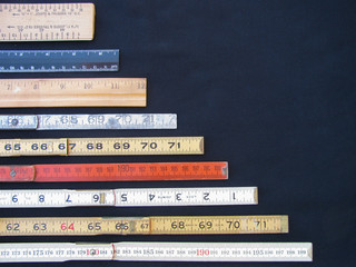 Rulers and scales in metric and inches represent measurement, accuracy and results with copy space. Graphic indicates large numbers at base declining to smaller at top.