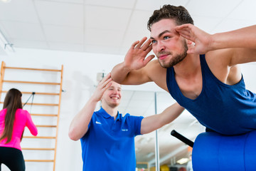 Athlete and his physiotherapist during exercise at workout equipment in health club gym