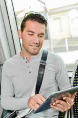 Man on public transport, looking at tablet