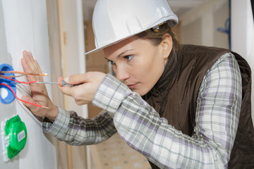 female electrician fixing socket electricity problem