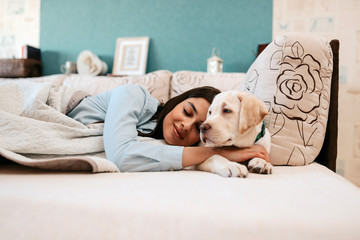 Attractive young girl with dog laying on a bed.
