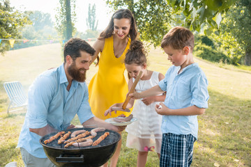 Dedicated father helping his son to use wooden tongs for putting sausages on the charcoal barbecue grill outdoors during family picnic in summer