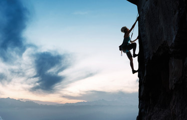 Young woman on the cliff rock climbing